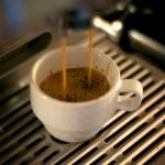 Imagem de uma xícara de café sob a máquina de café espresso, com o líquido caindo na xícara.