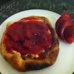 imagem da tortinha de morango: a massa enrolada como esfiha e o creme vermelho de morangos em cima. Sobre um prato branco com borda preto e branca. Ainda no prato, um morango fresco cortado verticalmente, como enfeite.