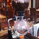 Imagem da cafeteira globinho durante o preparo, já com água pela metade no globo inferior e o café líquido se formando no globo superior.