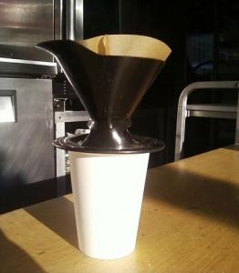 Imagem de uma xícara sobre a mesa com um coador de café.