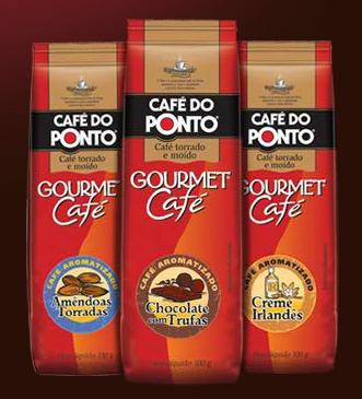 """imagem das embalagens de cafés aromatizados do café do ponto. Trata-se de uma embalagem de alumínio retangular, com o  da empresa e o título """"Gourmet Café"""" e um rótulo circular especificando o sabor. Na foto, há três opções: Amendoas Torradas, Chocolate com trufas e Creme Irlandês."""