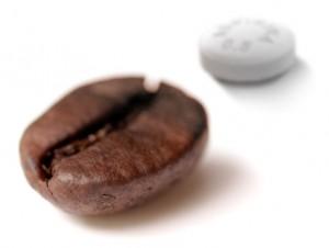 Grão de café com comprimido de Aspirina ao fundo
