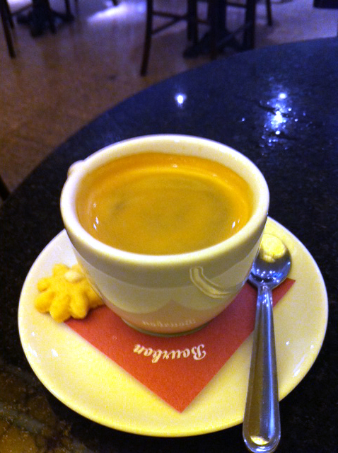 Imagem de uma xícara de café expresso sobre o pires. Ao lado, uma pequena colher e um biscoitinho em forma de estrela.