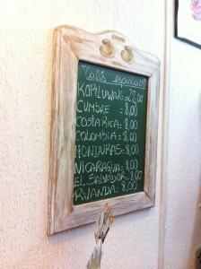 Imagem de uma pequena lousa, com nomes dos países de origem dos cafés, bem como o preço da xícara.