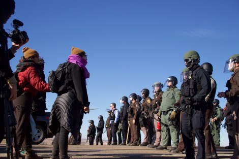 Pipeline opponents hold the line on Veteran's Day, 2016. At the camp, hundreds of Native American veterans marched as close as they could get to the pipeline construction site and prayed. Image Credit: Greg Harman