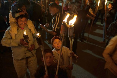 A child lights his brother's torch during the march in memory of Berta Cáceres on March 2. Image: WNV/Jeff Abbott.