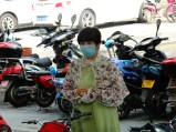 Local lady wearing a mask and a hand-modified shawl created from a shirt.