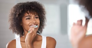 African American woman brushing teeth.