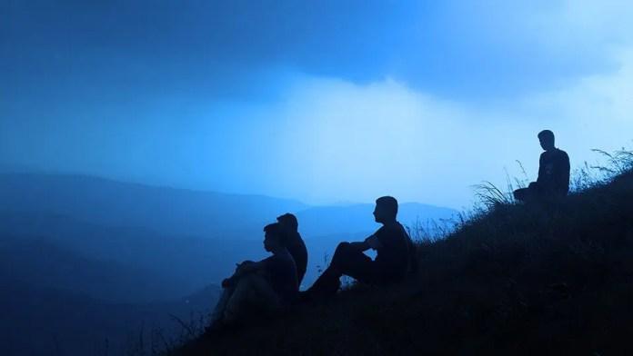एक पहाड़ी पर ध्यान में दोस्तों का समूह