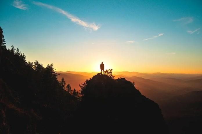 पहाड़ी के ऊपर से सूर्यास्त देख रहा आदमी