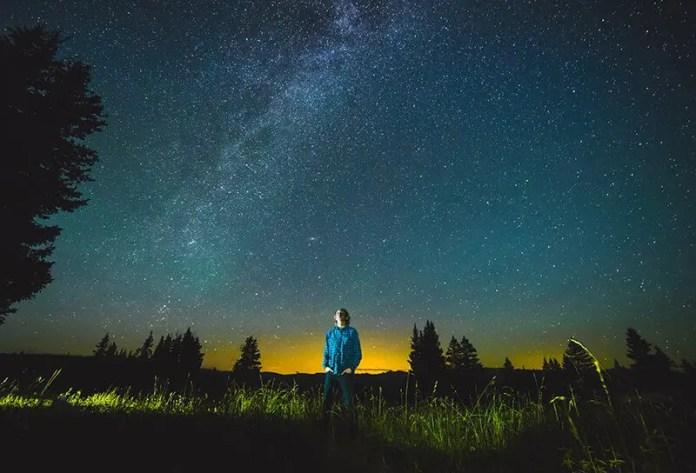 मनुष्य रात के परिदृश्य में विचार में खो गया