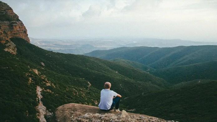 पहाड़ी की चोटी पर बैठा हुआ आदमी