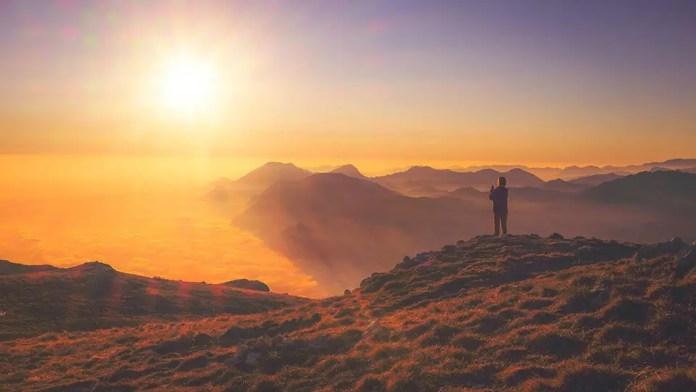 अस्त होते सूर्य की फोटो लेती महिला