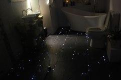 Suelo del cuarto de baño imitando una noche estrellada con fibra óptica