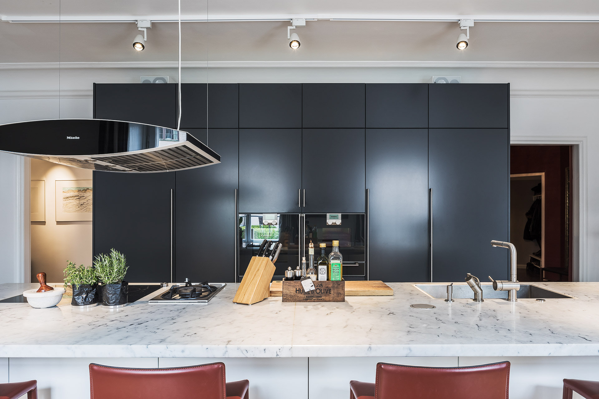 кухня темные фасады шкафы столешница мрамор плита вытяжка барные стулья