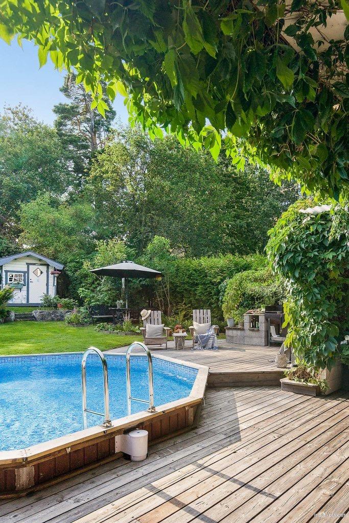 загородный дом бассейн деревянный настил газон кустарники