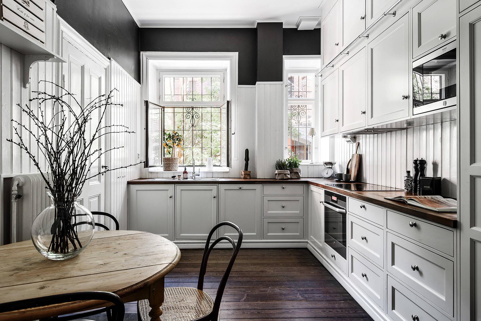 кухня белые фасады деревянный пол окна круглый стол
