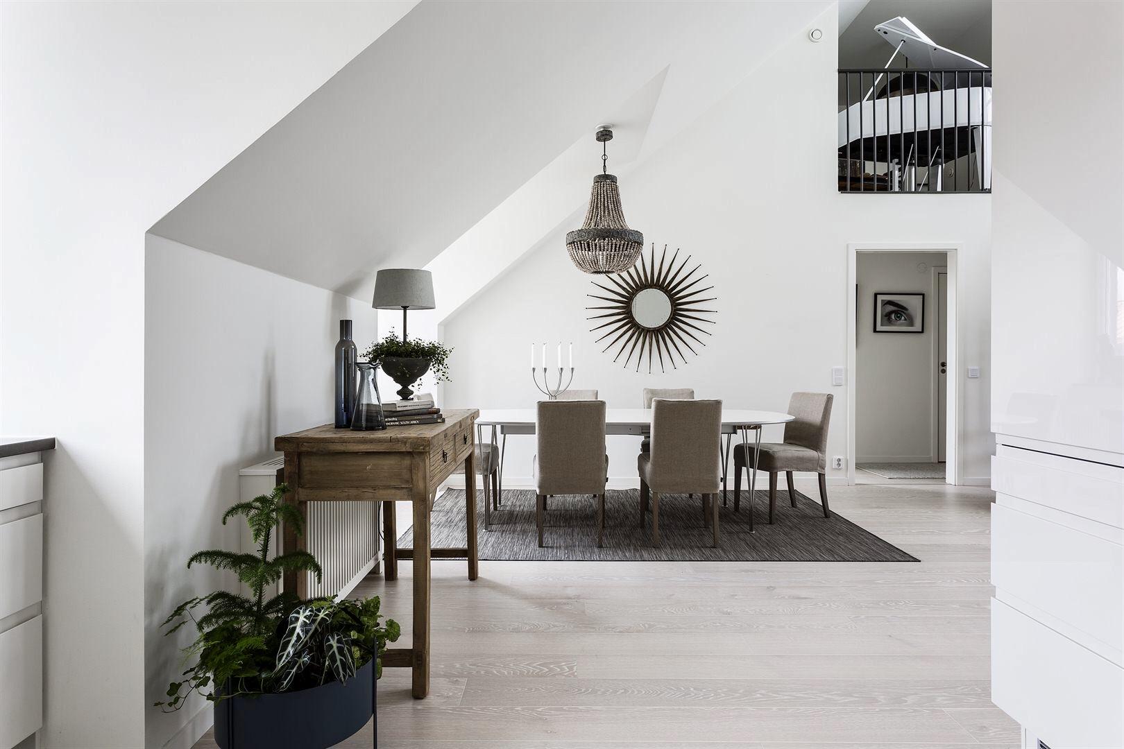 кухня столовая обеденный стол люстра над столом белые стены деревянная консоль