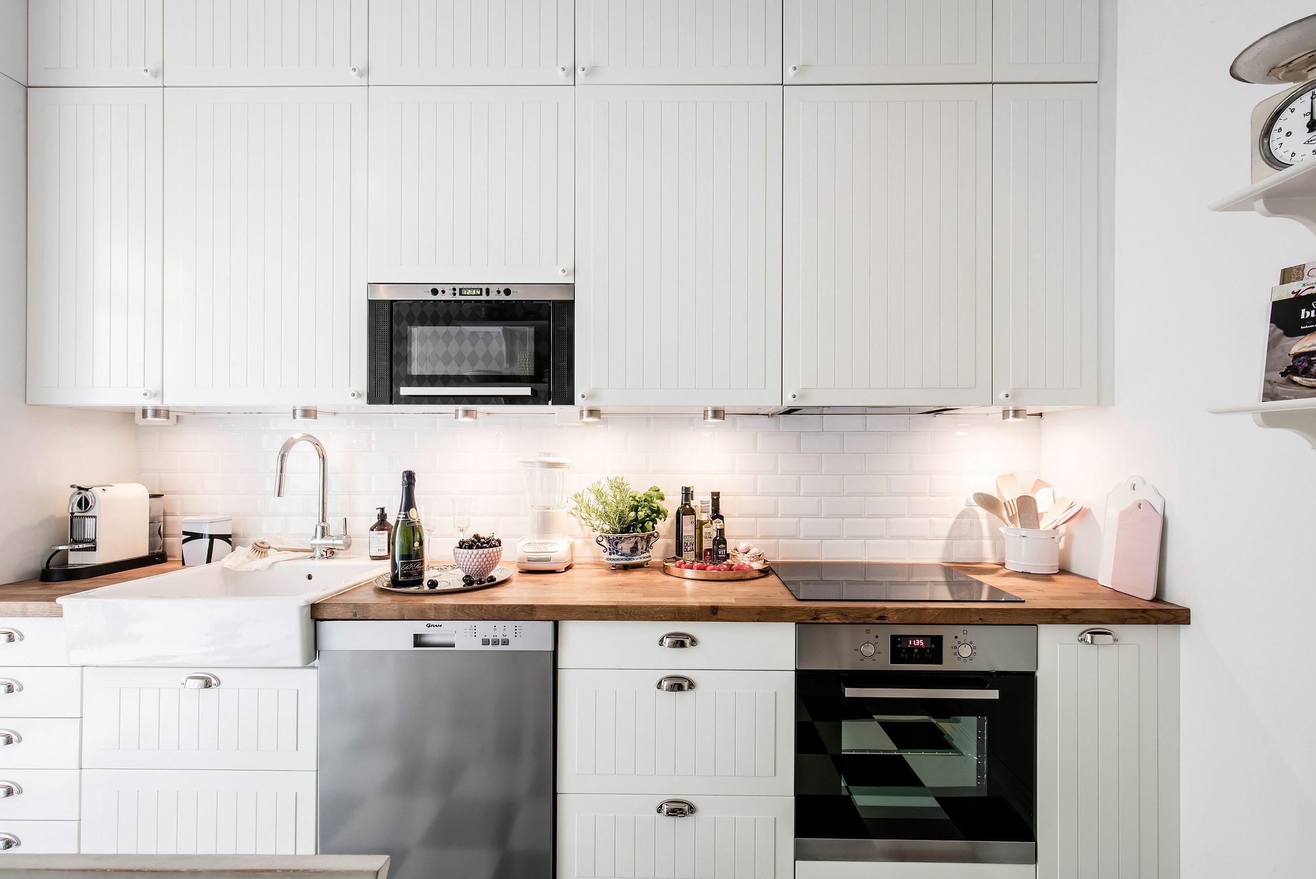 кухонная мебель белые фасады деревянная столешница встроенная вытяжка варочная панель духовка посудомоечная машина плитка кабанчик