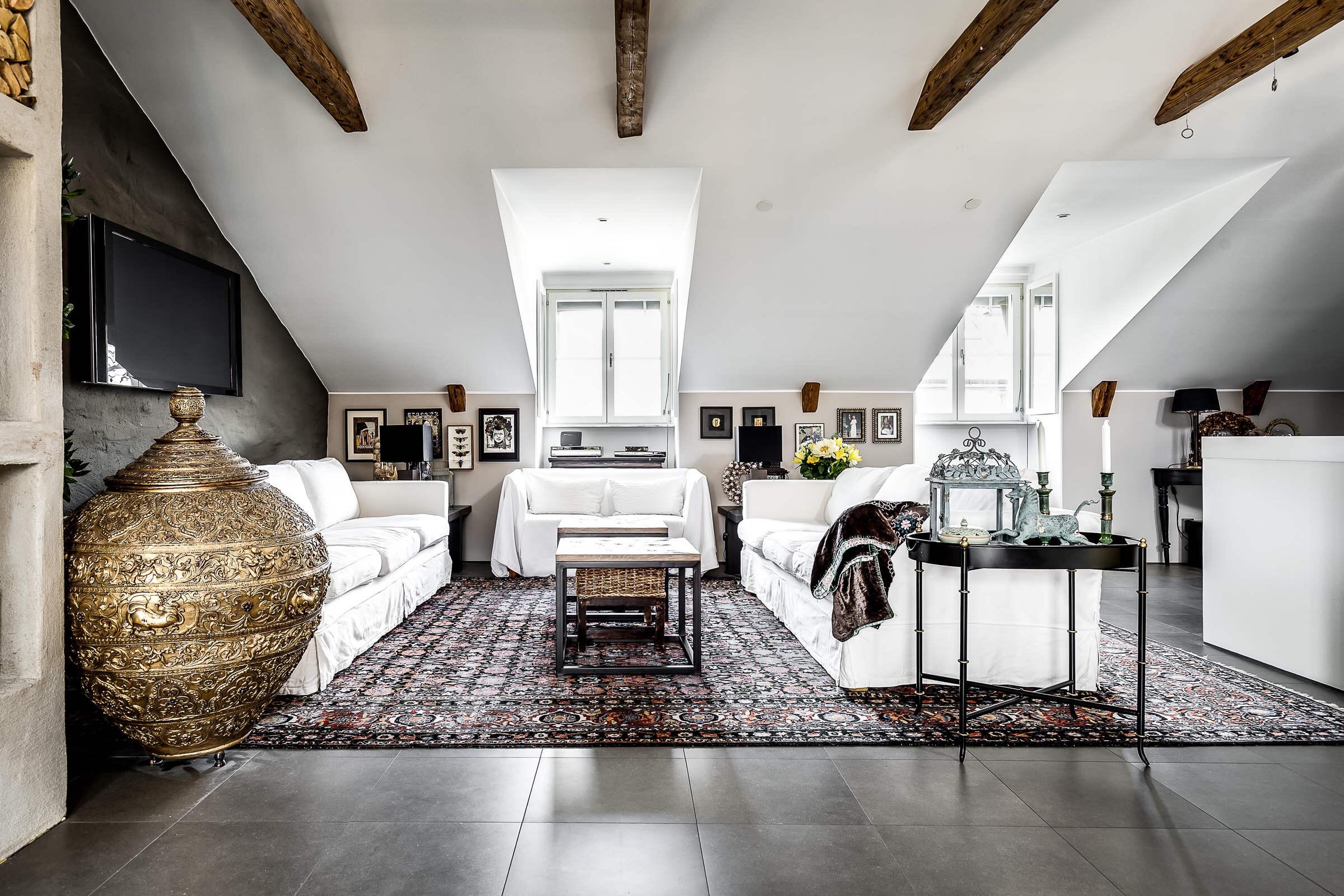 мансарда белые стены высокий потолок балки диван ковер телевизор столик