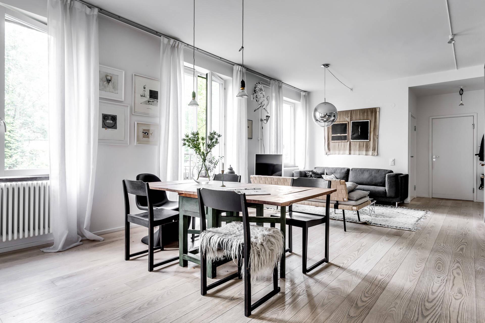 светлые стены деревянный пол обеденный стол диван телевизор панно