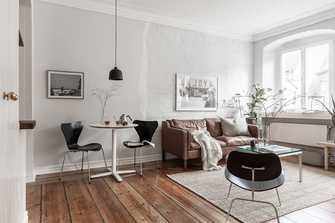 комната кожаный диван серые стены деревянный пол ковер