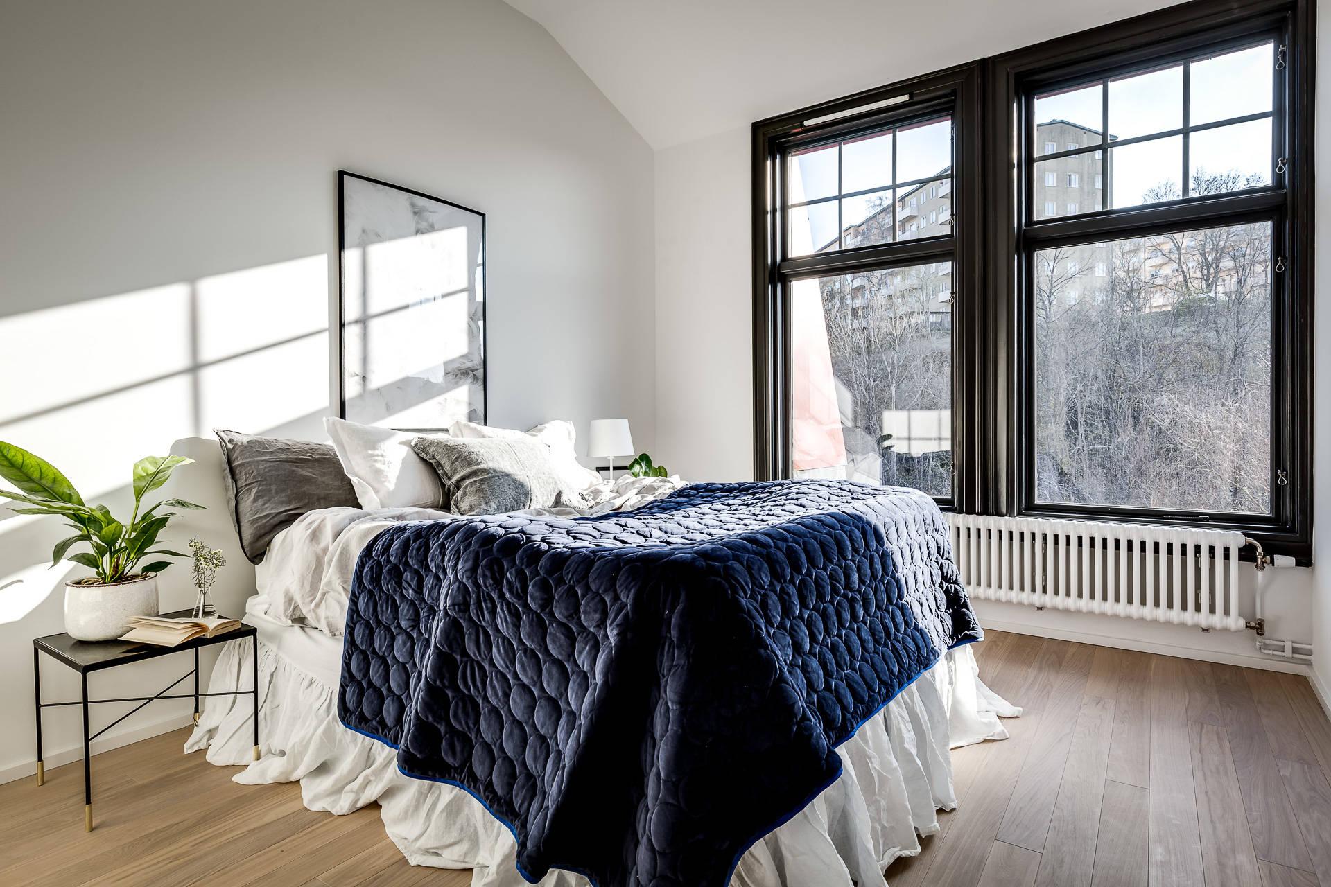 спальня кровать текстиль прикроватные столики окно темные рамы половая доска