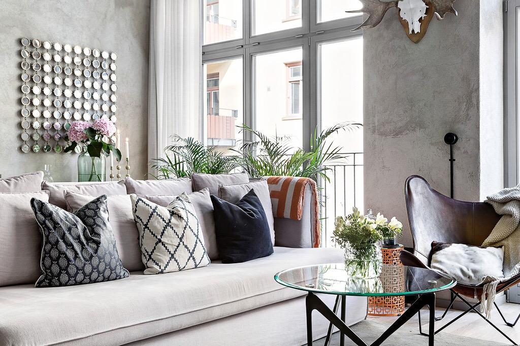 серый диван подушки комнатные растения стены микроцемент
