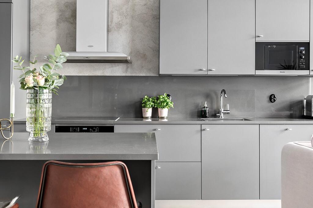 кухонная мебель серые гладкие фасады столешницв варочная панель духовка вытяжка барные стулья