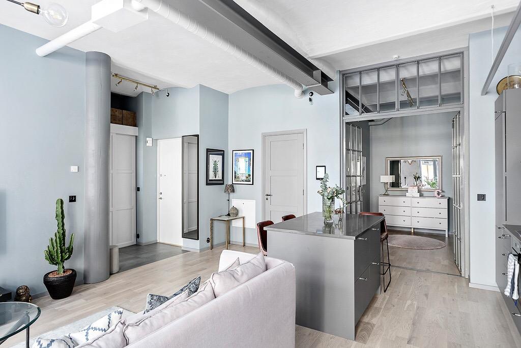 гостиная стеклянная перегородка высокий потолок своды кухонный остров барные стулья диван