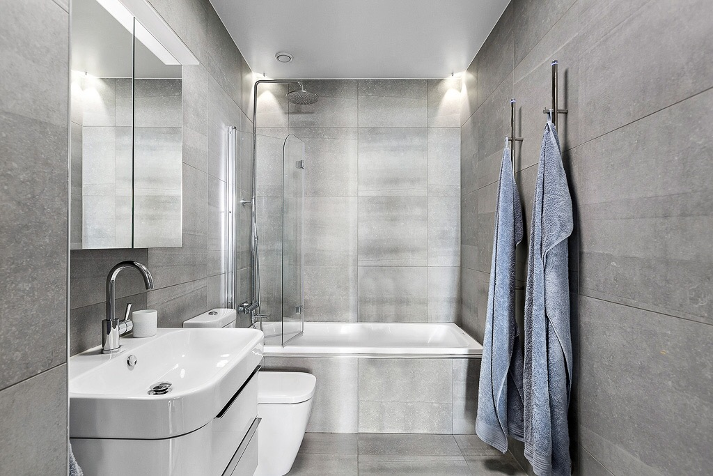 ванная комната ванна серая плитка душ раковина комод зеркало
