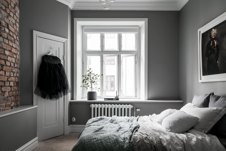 спальня серые стены окно подоконник цветок кирпичная кладка кровать текстиль