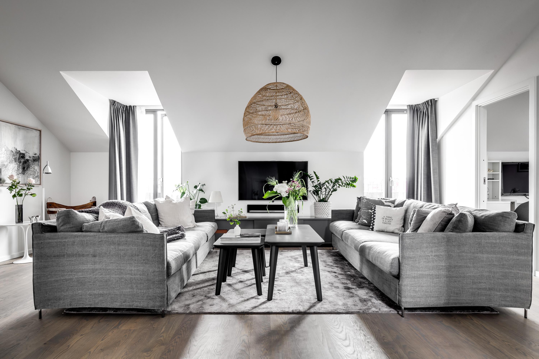 мансарда гостиная высокий потолок окна серые диваны столик телевизор