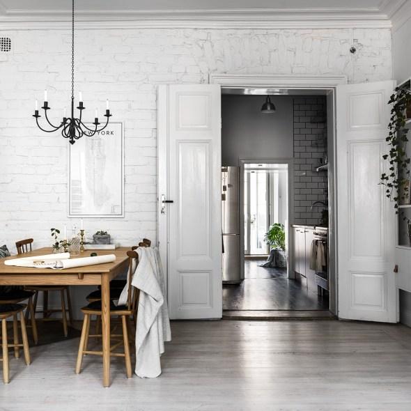 комната кирпичная кладка побелка распашные двери обеденный стол стеллаж высокий плинтус потолочный карниз