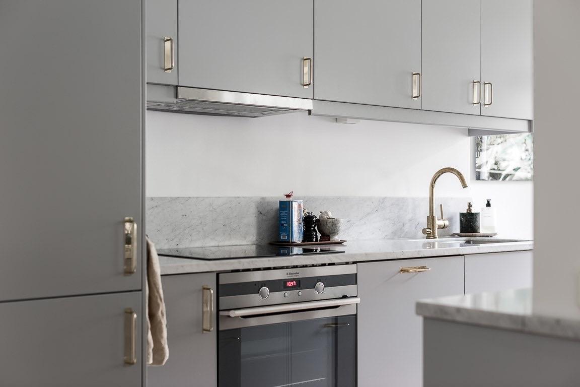 кухонная мебель серые гладкие фасады мраморная столешница фартук варочная панель духовка встроенная вытяжка