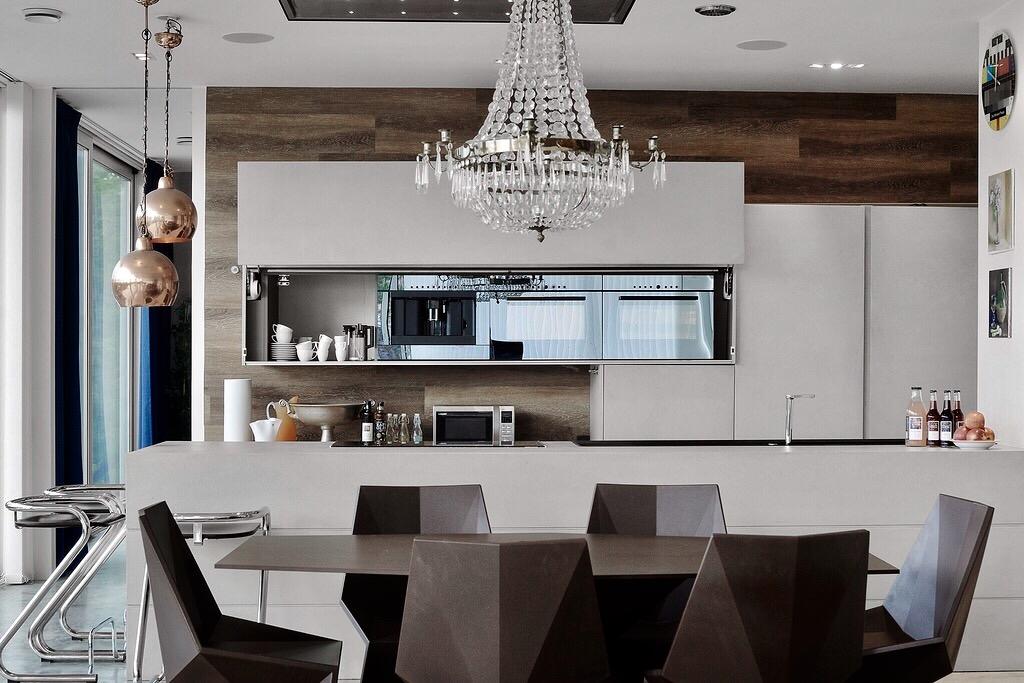 кухня белые фасады хрустальная люстра обеденный стол