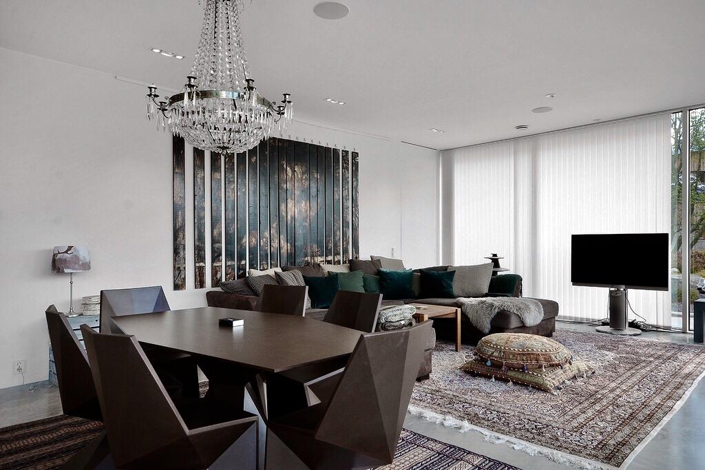 гостиная белые стены панно диван ковер подушки стол люстра
