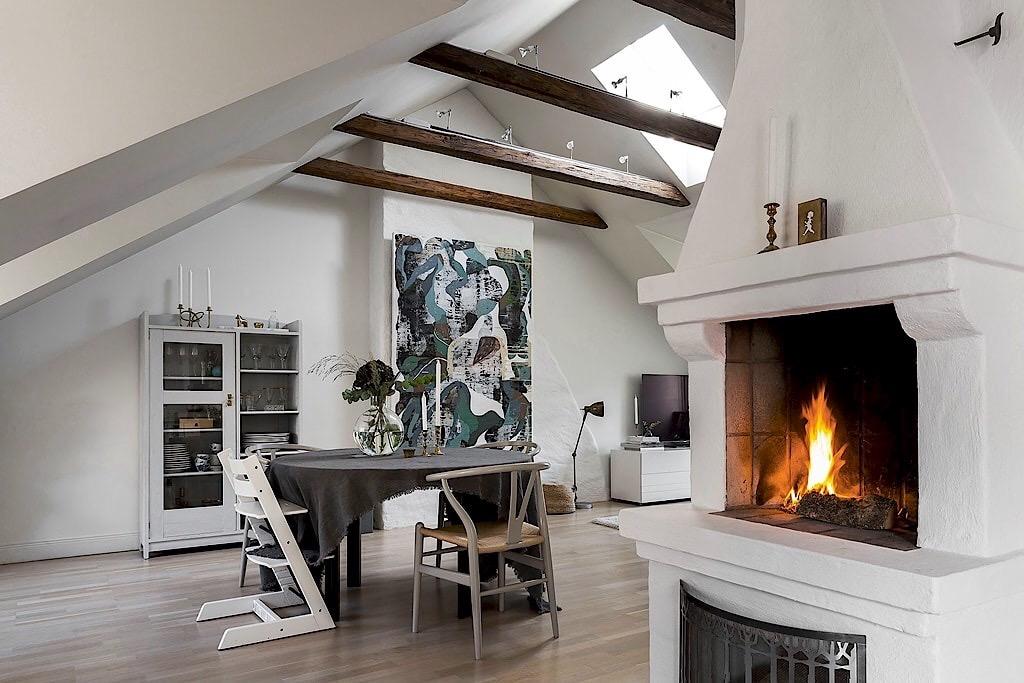 мансарда высокий потолок балки обеденный стол стулья скатерть камин шкаф витрина посуда