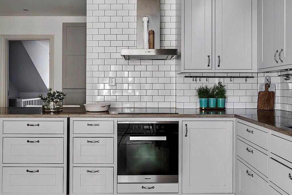 кухонная мебель серые фасады филёнка белая плитка кабанчик мраморная столешница варочная панель духовка вытяжка