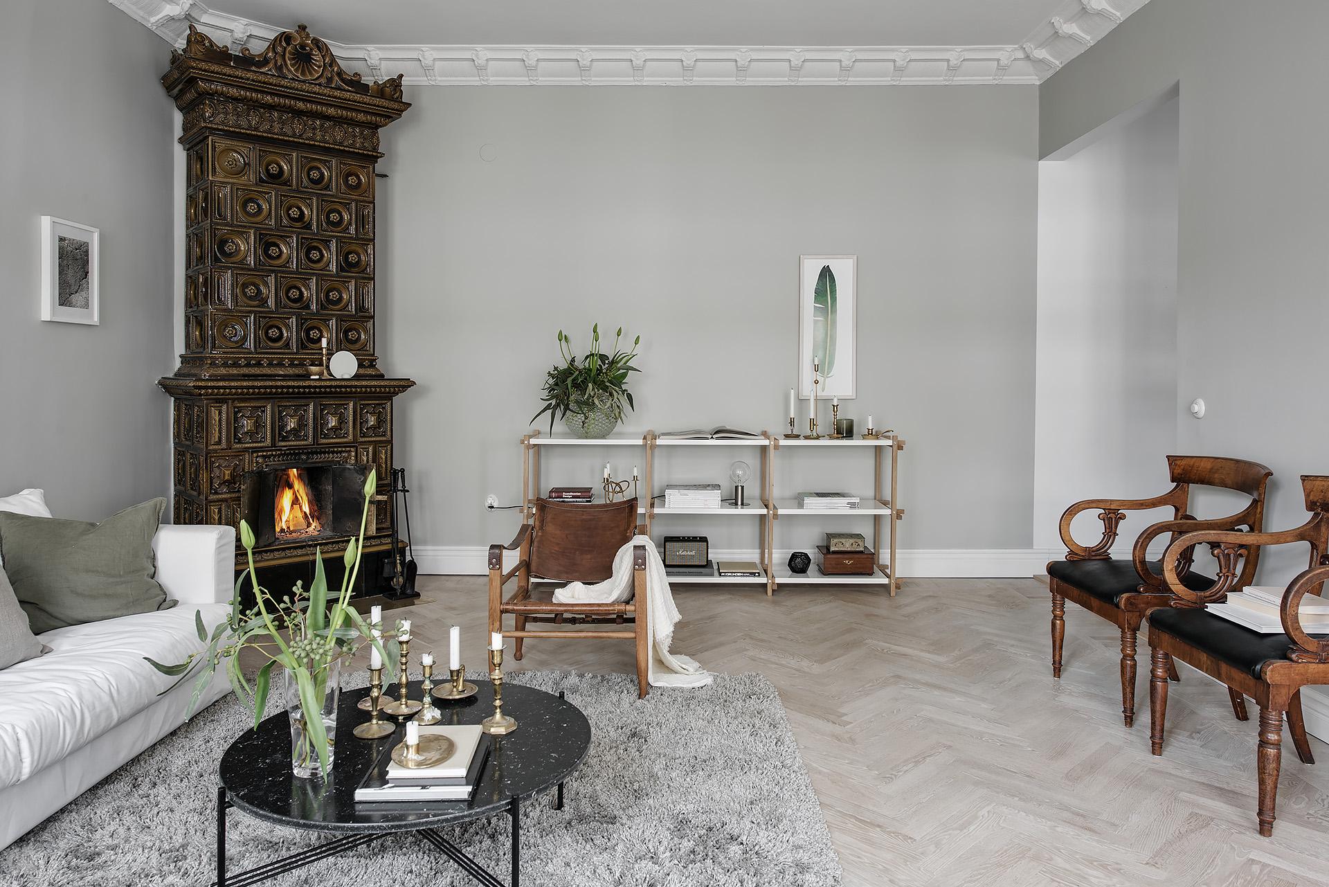 паркет елочка серые стены потолок лепнина карниз стеллаж скандинавская израсцовая печь кожаное кресло серый ковер