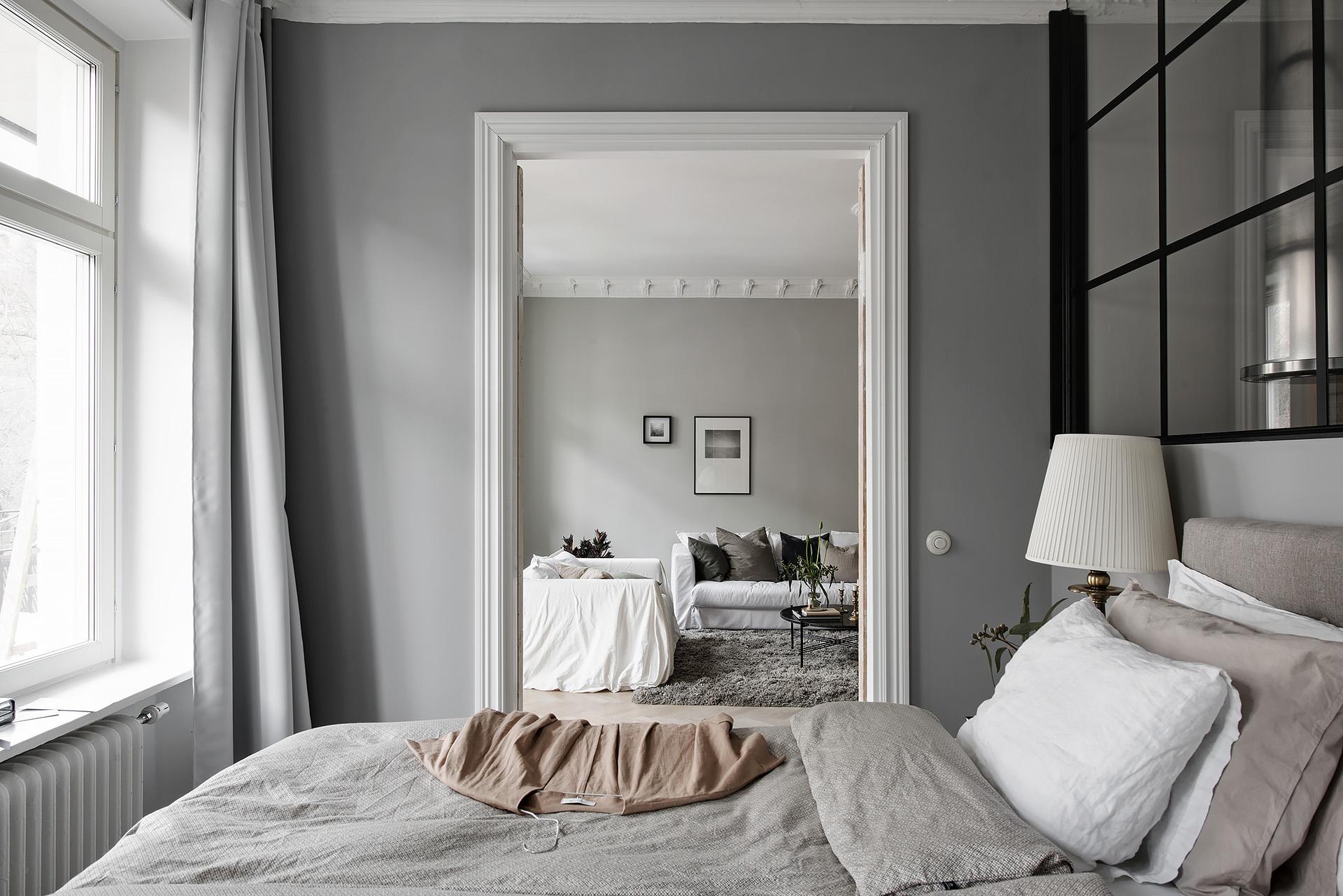 спальня проем наличники серые стены сварная стеклянная перегородка кровать текстиль прикроватные лампы