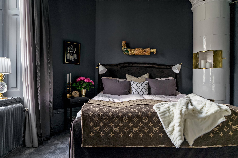 серые стены спальня кровать изголовье текстиль подушки окно откосы радиатор отопления израсцовая печь