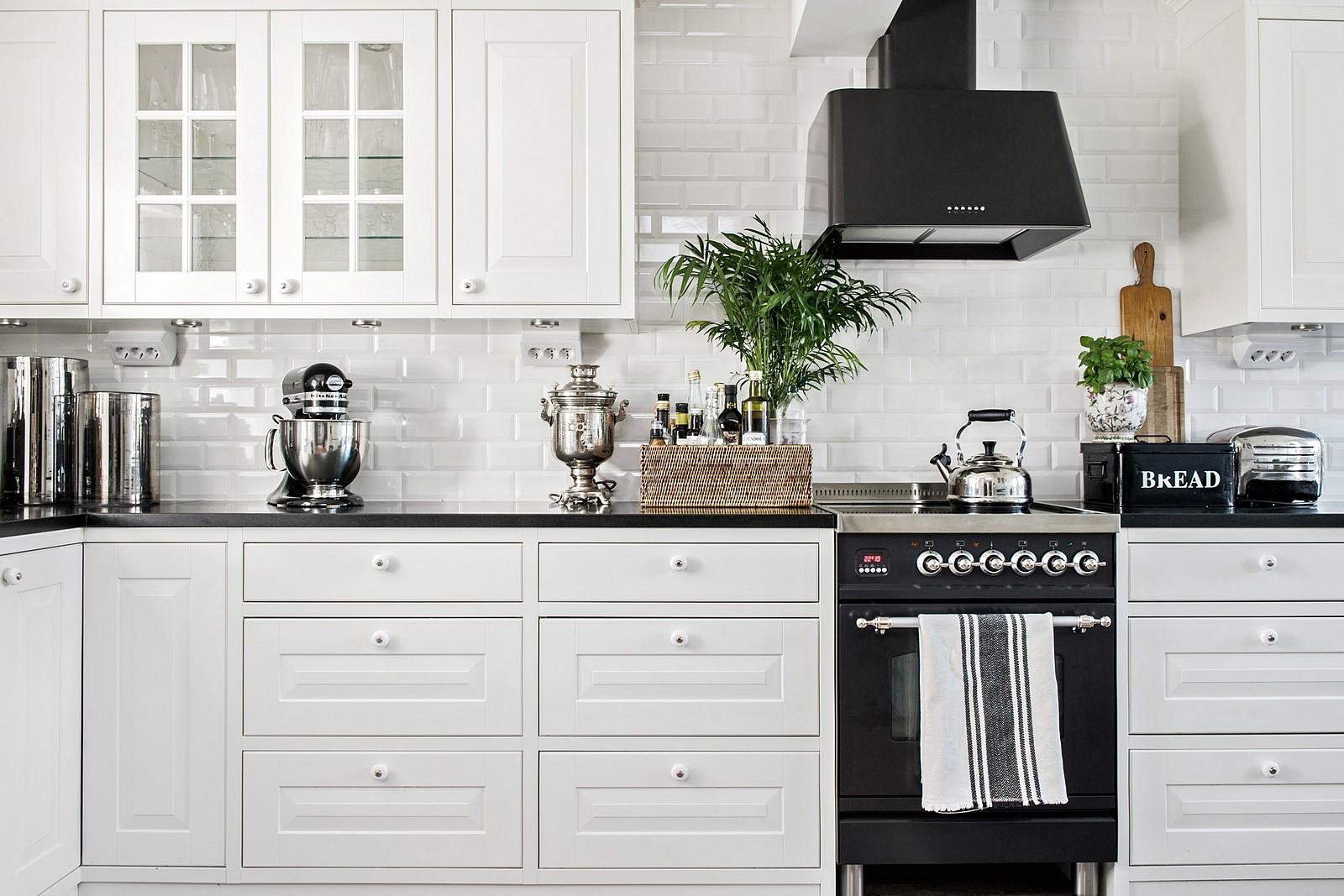 кухня плитка кабанчик белые фасады филёнка черная столешница плита вытяжка кухонные аксессуары