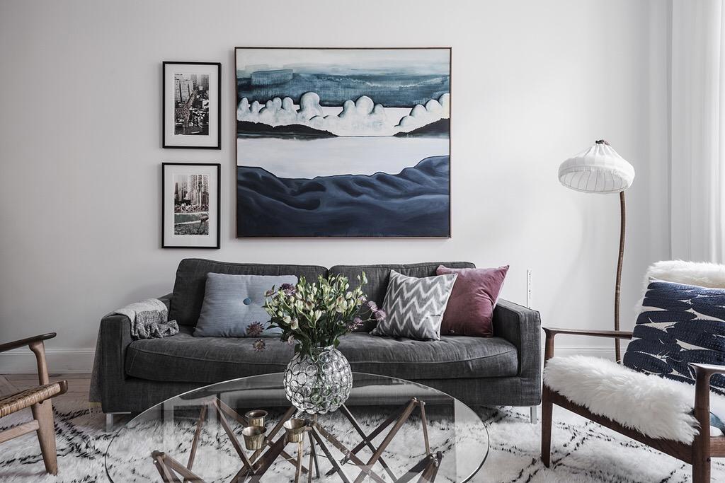 серый диван подушки торшер абажур круглый стеклянный столик ваза цветы панно ковер
