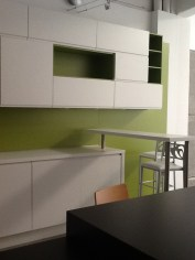 Una cocina con barra y gran capacidad de almacenaje. Con un fondo verde que dificulta el trabajo de deciración. A ver que hacemos en esta cocina