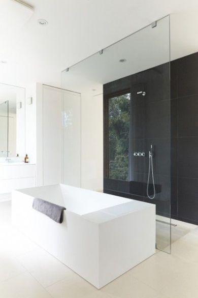 Baño minimalista en blanco y negro. La bañera queda centrada y sirve de apoyo a la mampara de la ducha