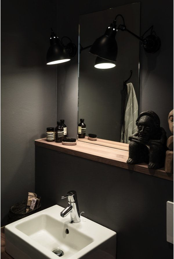 Baño con paredes muy oscuras, típico del estilo masculino