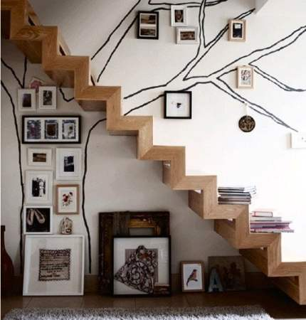 white walls and family tree under stairs
