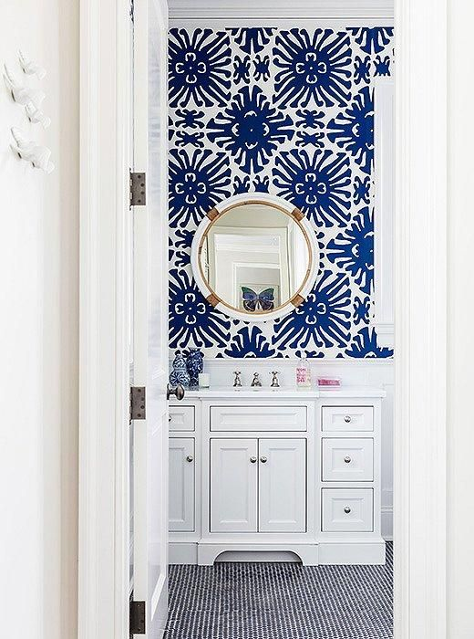 """Obsessed with the bold cobalt blue and white geometric sunburst patterned wallpaper and shiny brass and chrome accents in this adorable bathroom.  Read more on our Style Guide, """"Inside Sue De Chiara's Gorgeous Connecticut Home That's  Both Totally Traditional and Full-On Fun!"""":"""