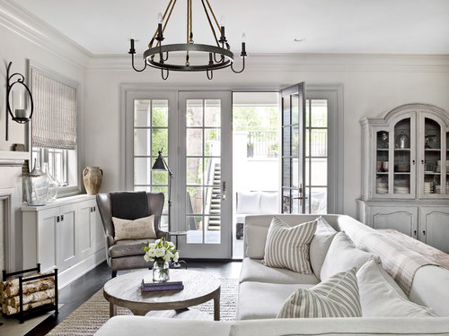 Beige designed living room with a round chandelier, couch and table with flowers in vase